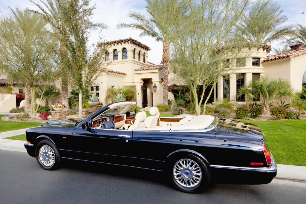 Black convertible car parked in front of luxury house