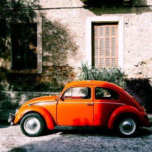 Orange Volkswagen Beetle in front of an old house