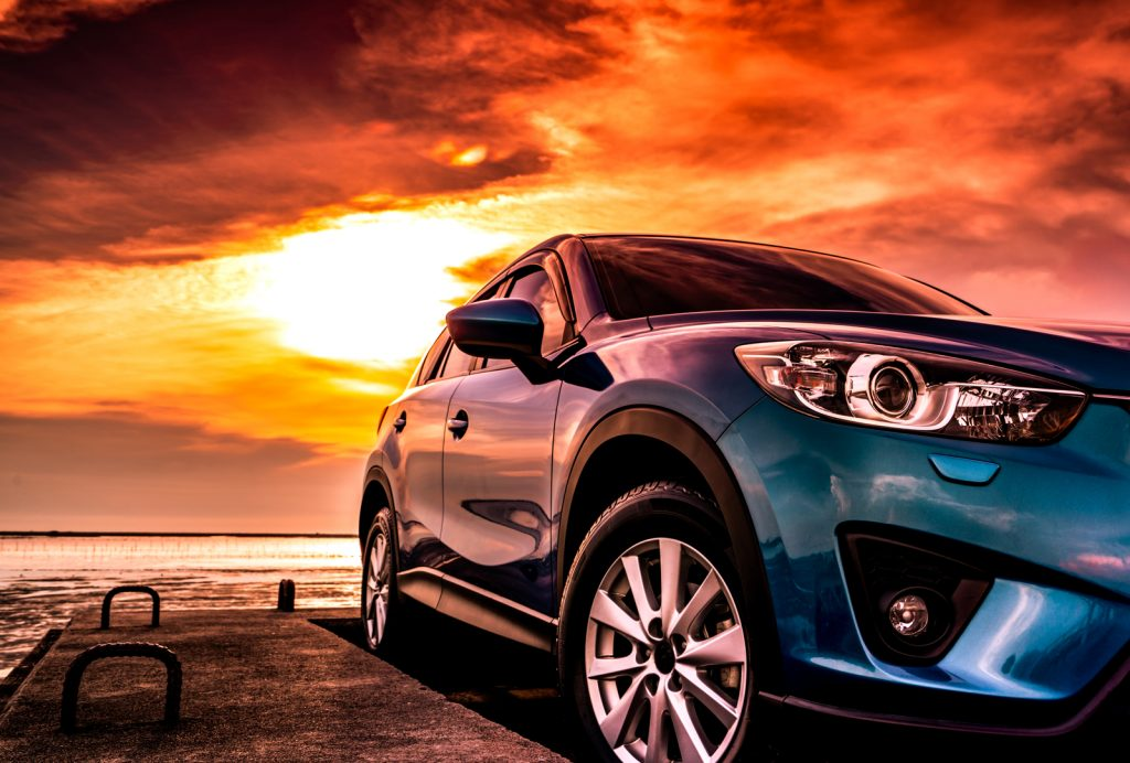 Blue compact SUV car with sport, modern, and luxury design parked on concrete road by the sea at sunset.