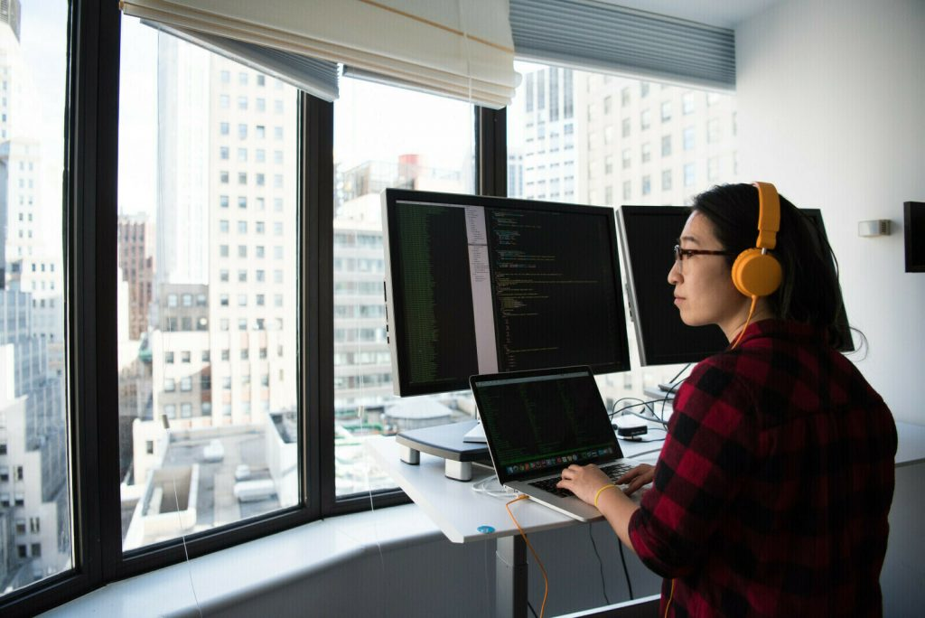 Women working on desk with a laptop and large monitors